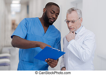 Gifted young doctor sharing opinion with aged colleague at...