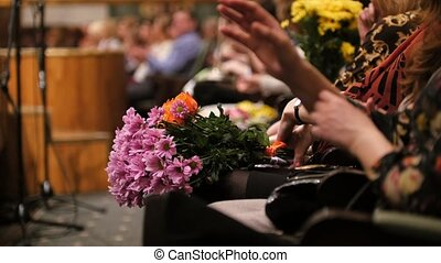Theater hal - spectators with flowers applauding the...