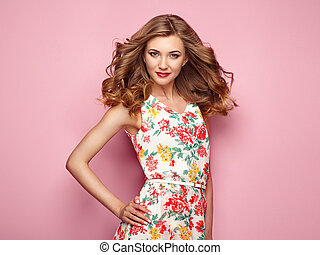 Blonde young woman in floral spring summer dress. Girl...