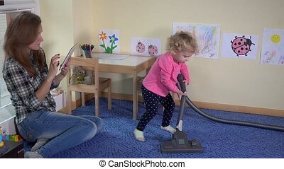 Mother woman using tablet computer and her little daughter girl hoovering floor