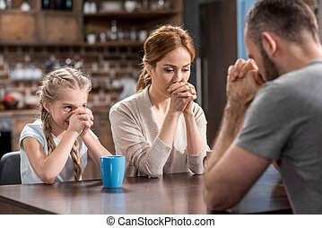 Young family praying while sitting at the table in kitchen
