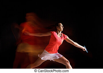 Young woman playing badminton over black background - Young...