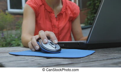 Young woman uses laptop outside - Medium shot of young woman...