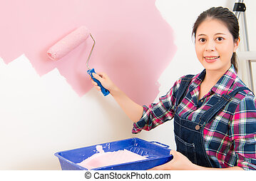 smiling woman painting wall at home