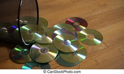 Several useless digital discs falling out of the dustbin....