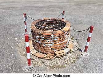 old well on the road with chain around