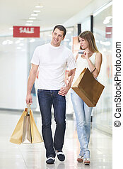 Shopping - An attractive couple with a credit card at the...