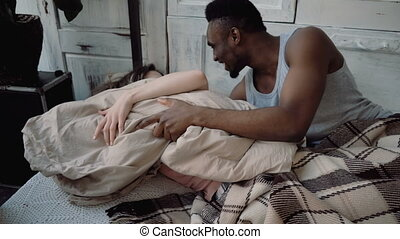 Multiracial couple spending time together. Male and female lying on bed, laughing. Man and woman fighting with pillows.