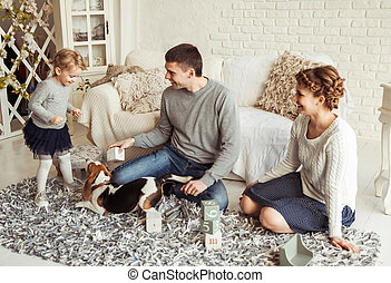 happy family playing with a pet dog in the spacious living...