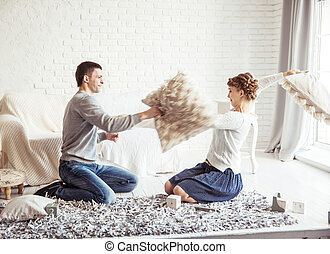 happy couple jokingly holds the pillow fight on the sofa in...