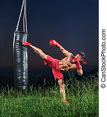 Young handsome male boxer practicing on a punching bag...