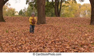 Happy playful kid throws autumn leaves in park. Three years...