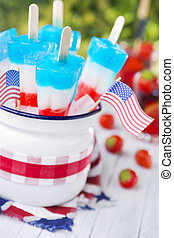 Red-white-and-blue popsicles on an outdoor table with summer...