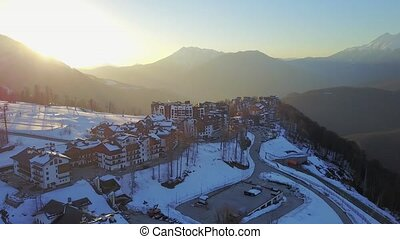 Sunset in the snowy mountains and buildings. Aerial, Rosa...