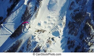 Paraglider flies over the mountains over the ski resort in...