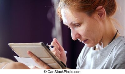 Portrait of woman at home sitting at sofa and working with gadget and notebook