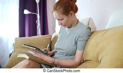 Woman at home sitting at sofa and working with gadget and notebook