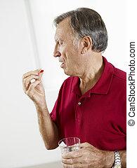 senior man eating pills - Senior man taking medicine...