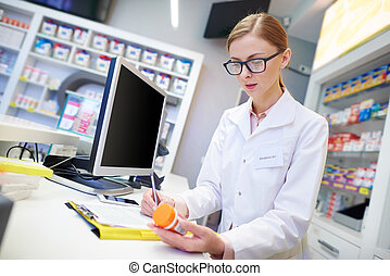 Mid adult pharmacist filling forms
