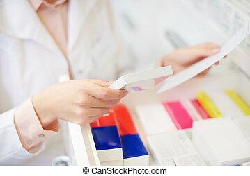 Pharmacist filling prescription at drugstore