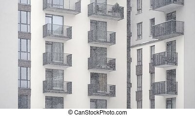 snowing in the yard of modern new building with balconies