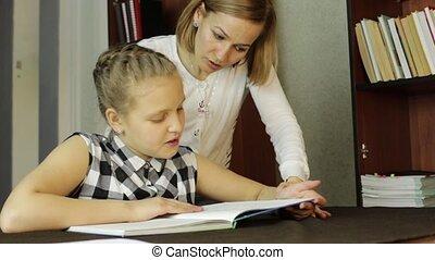 Upset little girl doing school tasks with mother, mom...