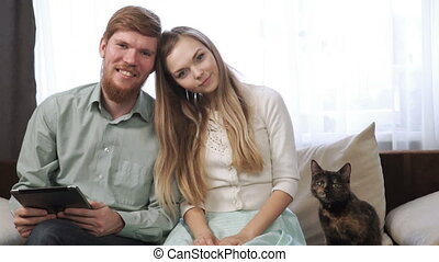 Couple A young man and a woman, and their cat is sitting on the couch sofa at home Look into the tablet and smile