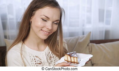 Attractive young woman sitting at cafe eating cake drinking tea using touchpad and smiling.