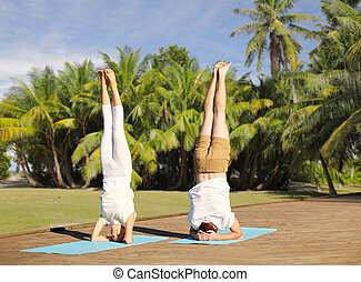 couple making yoga headstand on mat outdoors - fitness,...