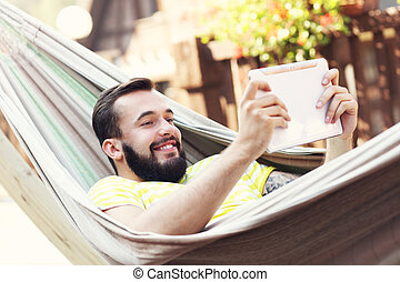 Picture showing happy man resting on hammock with tablet