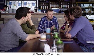 Friends sitting at the table in cafe enjoying leisure time together talking to each other. Students chatting while having lunch at the restaurant. People drinking beverages and having conversation.