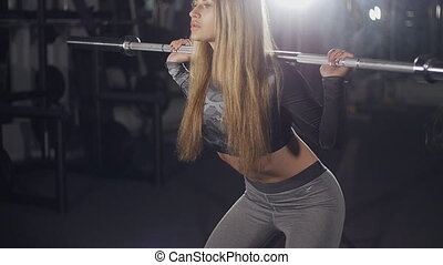 Young woman with beautiful athletic body doing exercises...