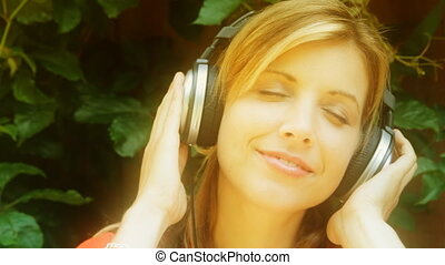 Young woman wheadphones Dreamy - A young woman closes her...