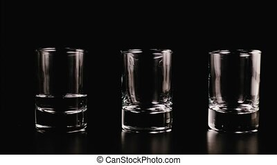 Vodka fills a glass on a black background. Stop motion,...