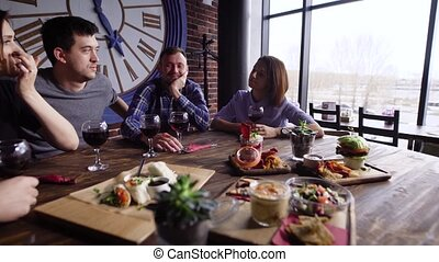 Five friends are holding glasses of red wine and sitting at the table served with different snacks in restaurant and having party. Men and women are spending leisure time in cafe near the window.