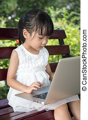 Asian Chinese little girl sitting on the bench with laptop...