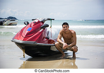 Handsome male posing near jet ski - Young muscular male...