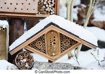 snow at insect hotel with wild bees and wesps.