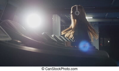 Young pretty woman running on treadmill - Young woman...