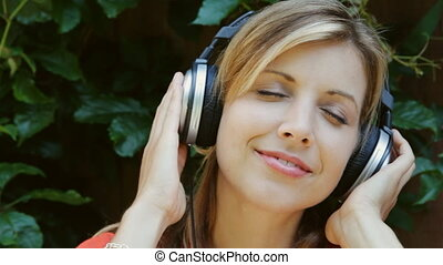 Young woman. Mellow headphones. - A young woman closes her...