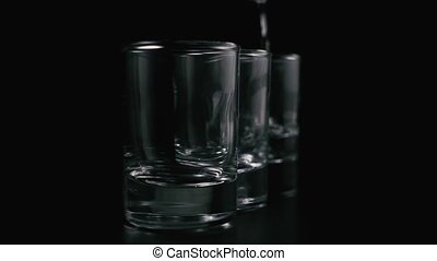 Tequila, vodka pours drops into the shots on a black...