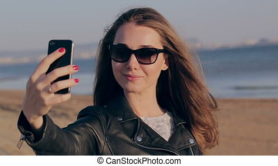 Summer vacation beach travel. Technology and people concept with smiling woman making selfie with smartphone on beach. Caucasian woman taking self portrait having fun