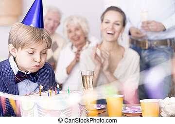 Child blowing out candles on birthday cake