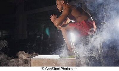 Athlete gave exercise. Jumping on the box. Fitness concept