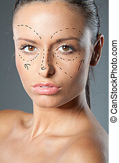 plastic surgery - Drawn lines on a brunette woman's face as...