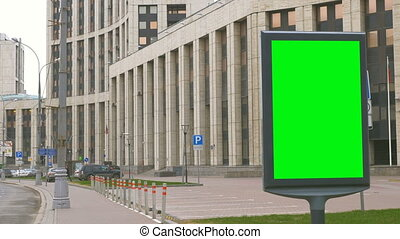 A Billboard with a Green Screen on a Busy Street. IIn the...