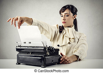 Woman working with typewriter - Young woman working with...