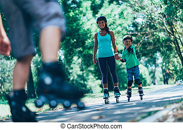 Family roller skating - Mother and son in bacground in focus...