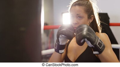 Hard hitting female boxer training in boxing club - Female...