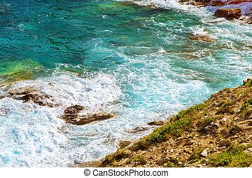 Waves break on rocky shore. Bali, Crete - Waves break on...